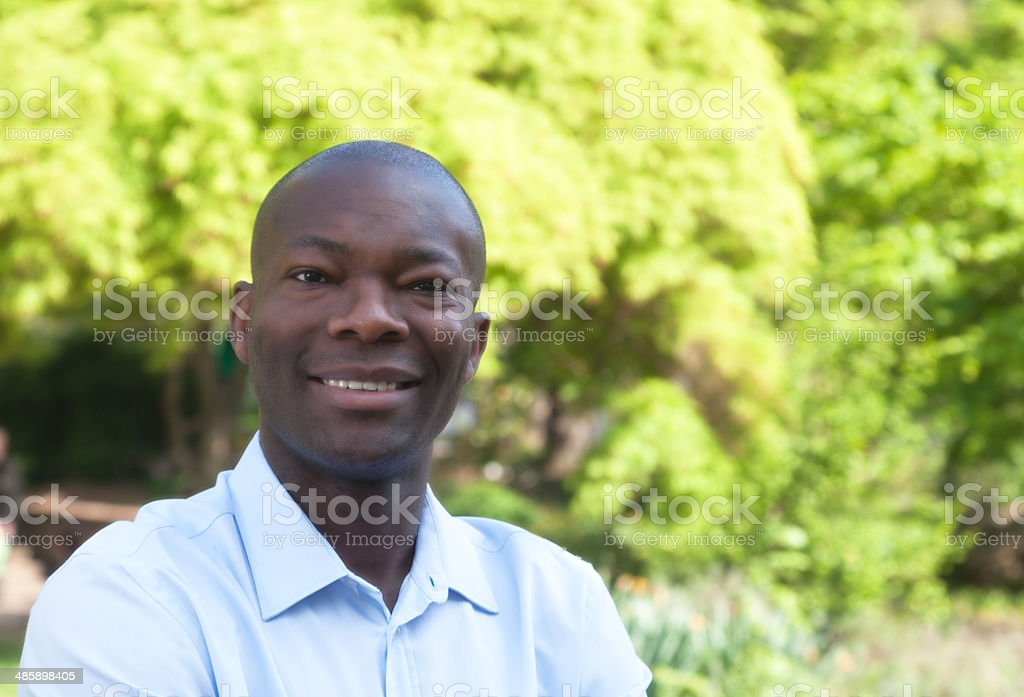 Happy african man in park looking at camera stock photo