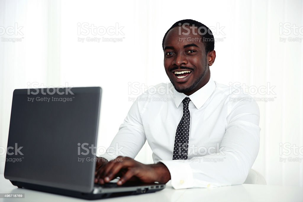 Happy african man using laptop royalty-free stock photo