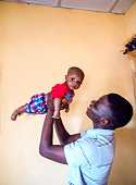 Happy African teenager playing with a baby