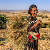 Happy African woman carrying straw, East Africa