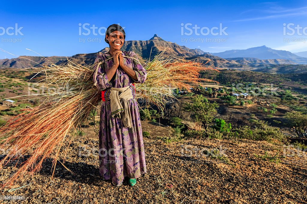 Happy African woman carrying straw, East Africa stock photo