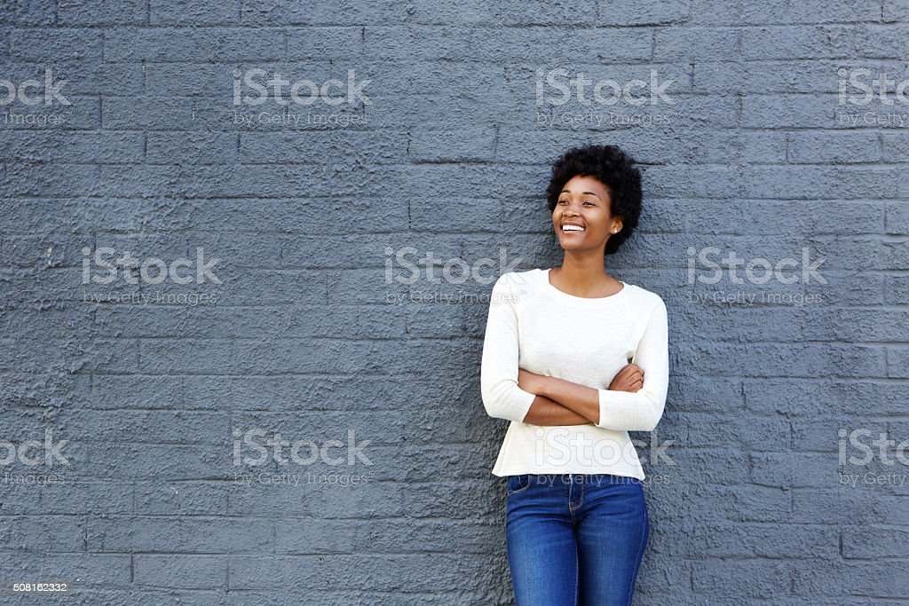 Happy african woman standing against a gray wall stock photo