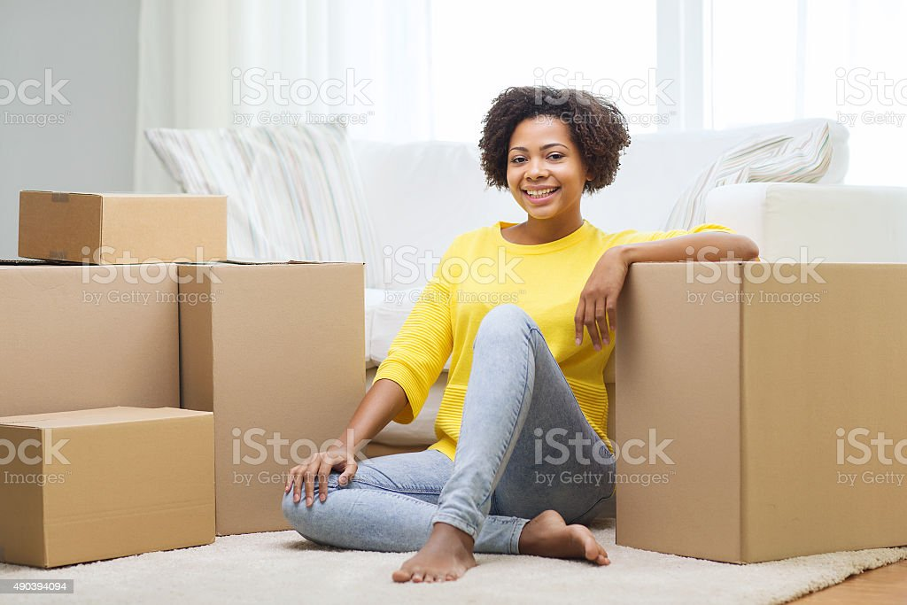 happy african woman with cardboard boxes at home stock photo