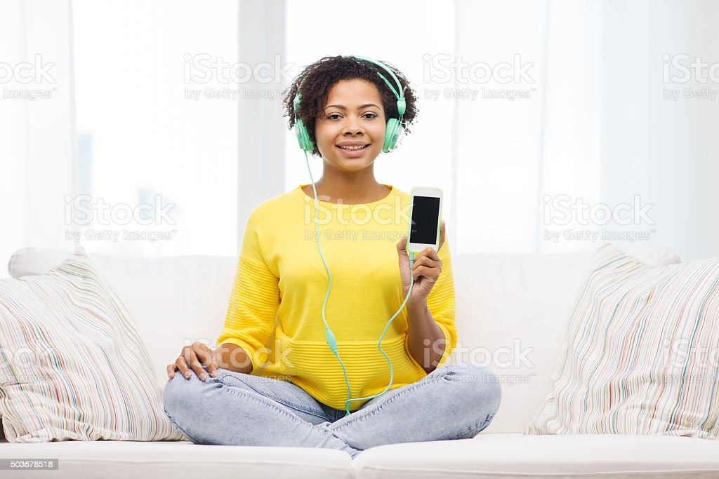 happy african woman with smartphone and headphones stock photo