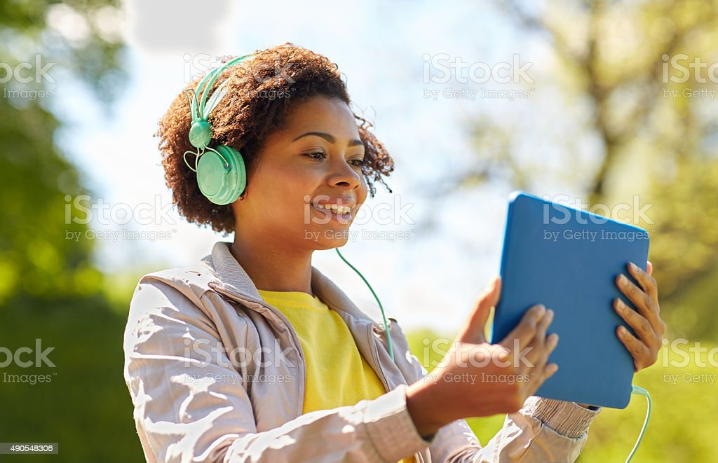 happy african woman with tablet pc and headphones stock photo