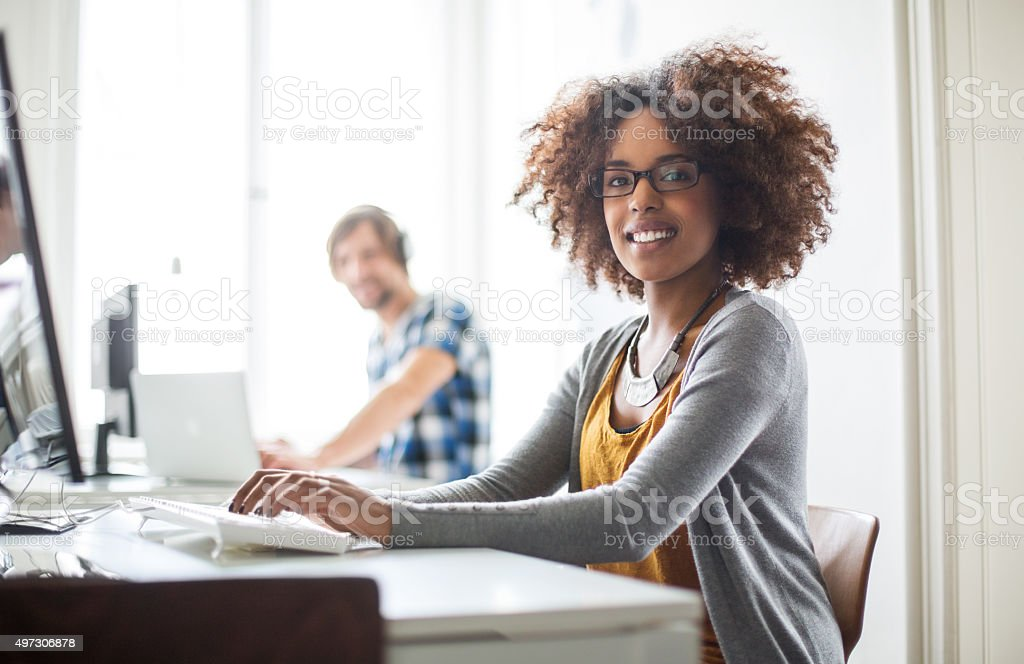 Happy african woman working at her desk stock photo