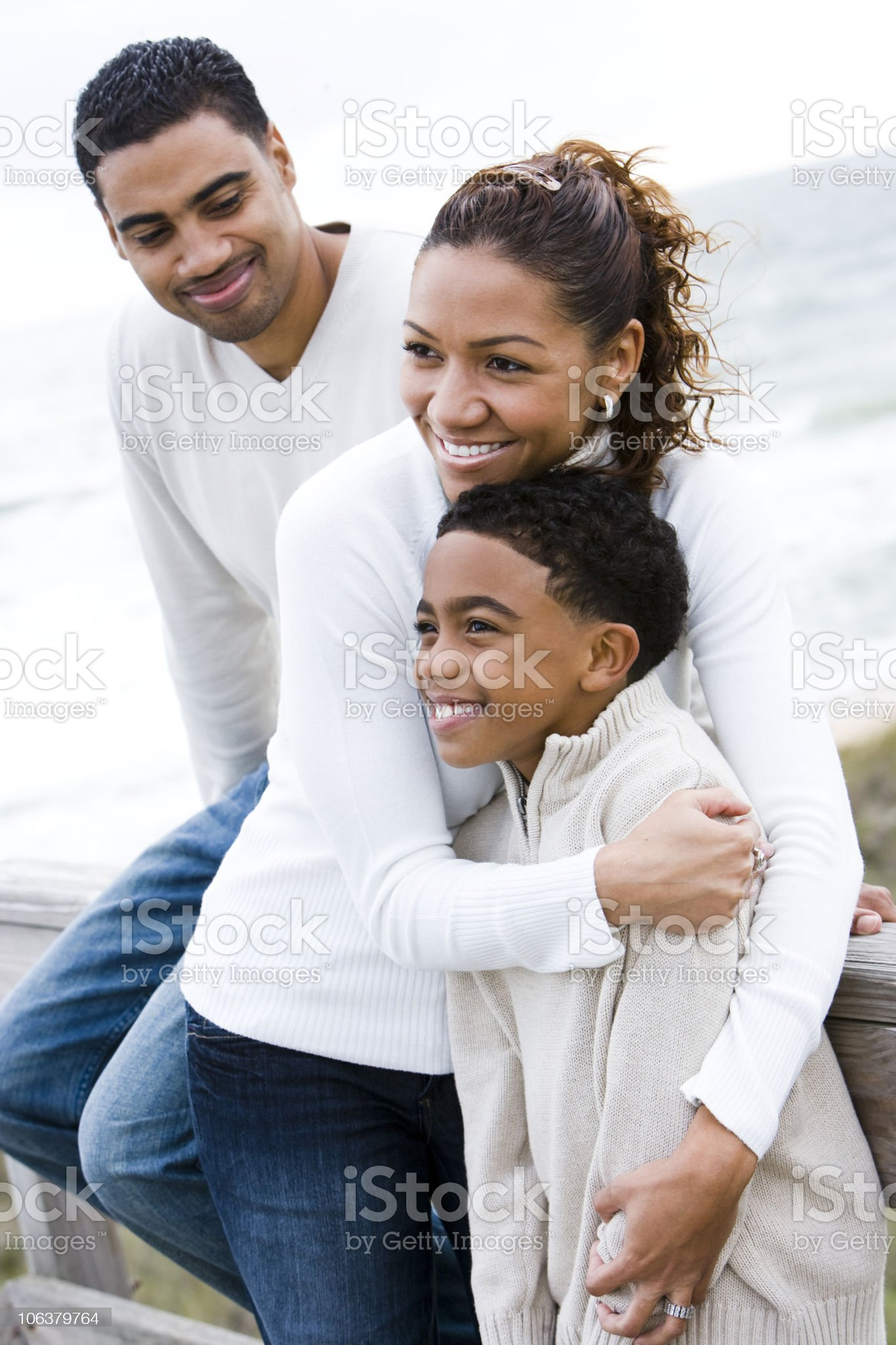 Happy African-American family in white tops at beach royalty-free stock photo