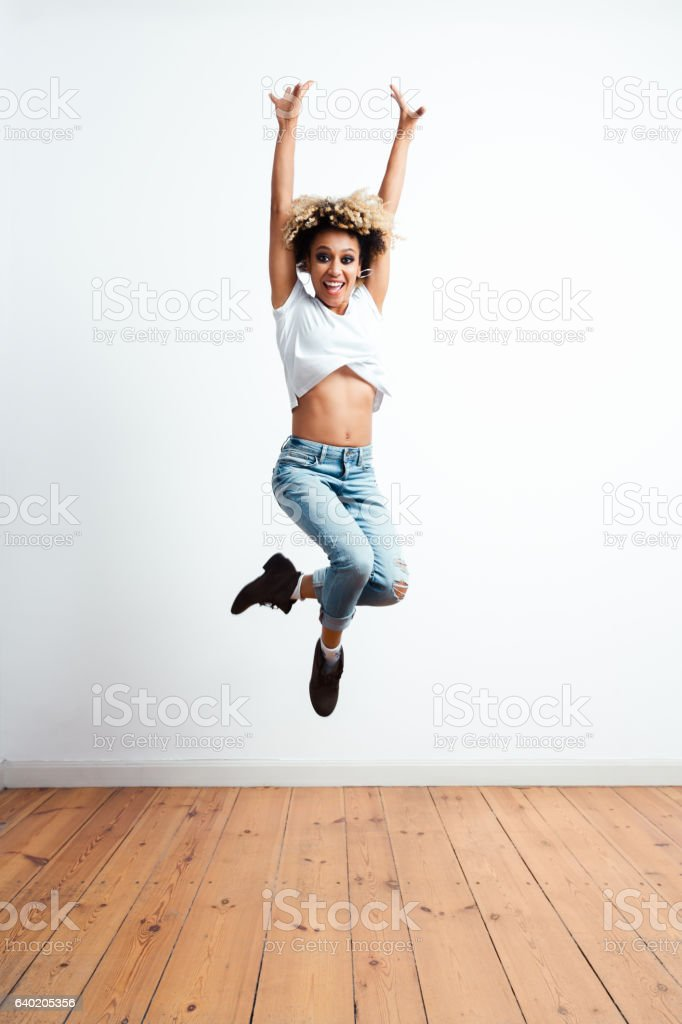 Happy afro american young woman jumping stock photo