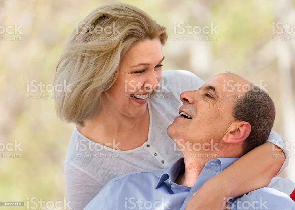 Happy aged man and woman hugging each other stock photo