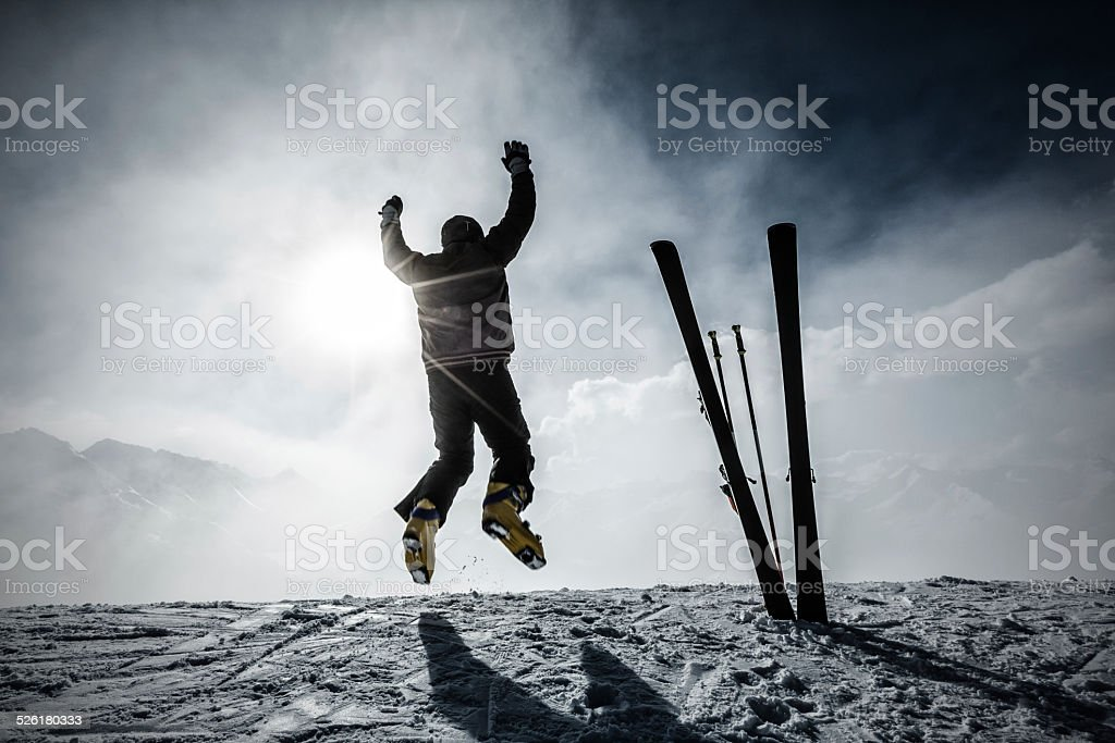 Happy alpine skier jumping in air on the top stock photo