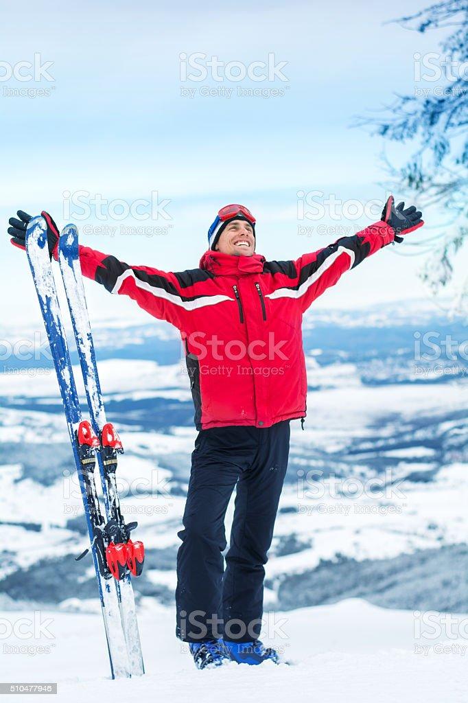 Happy alpine skier on the top stock photo