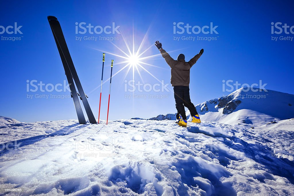 Happy alpine skier raising arms in air on the top royalty-free stock photo