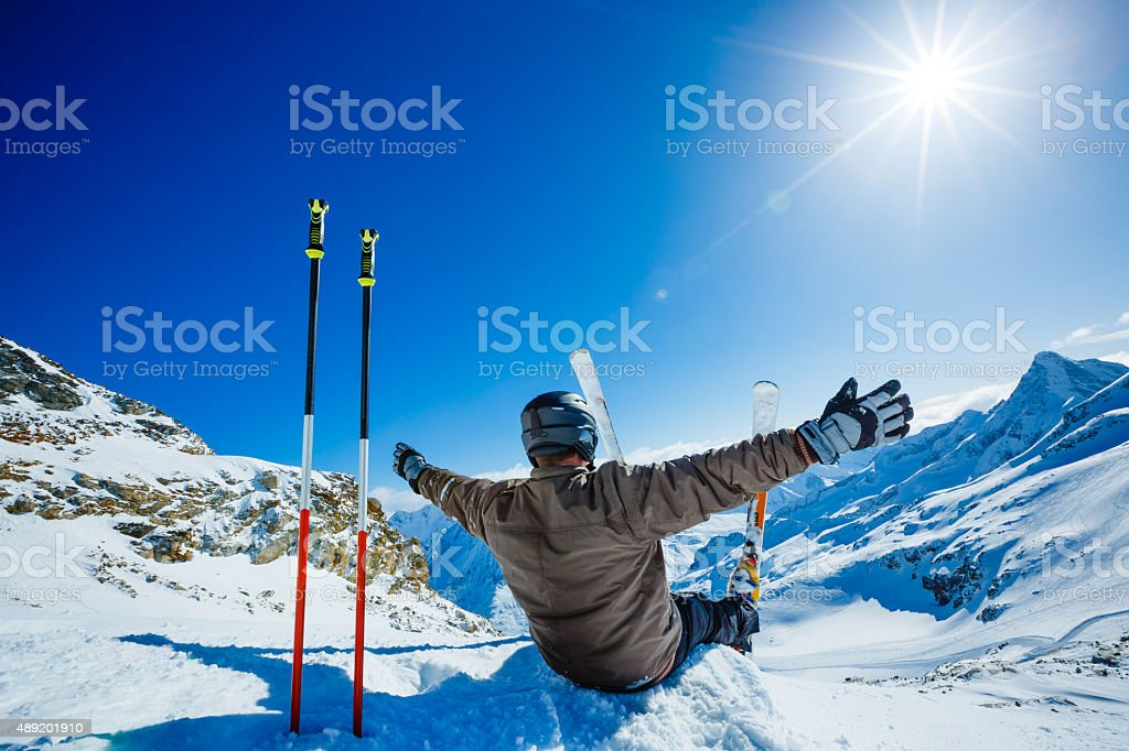 Happy alpine skier sitting on the edge stock photo