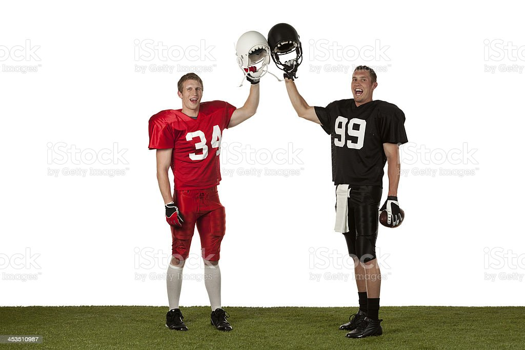 Happy American football players holding helmets stock photo