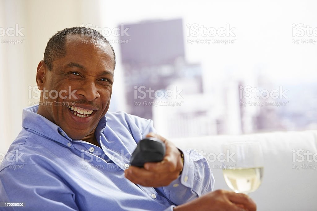 Happy American man sitting with glass of wine watching television royalty-free stock photo