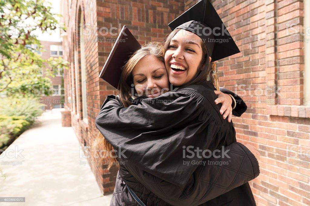 Happy American Mother Hugs Daughter Celebrating Graduation Day USA stock photo