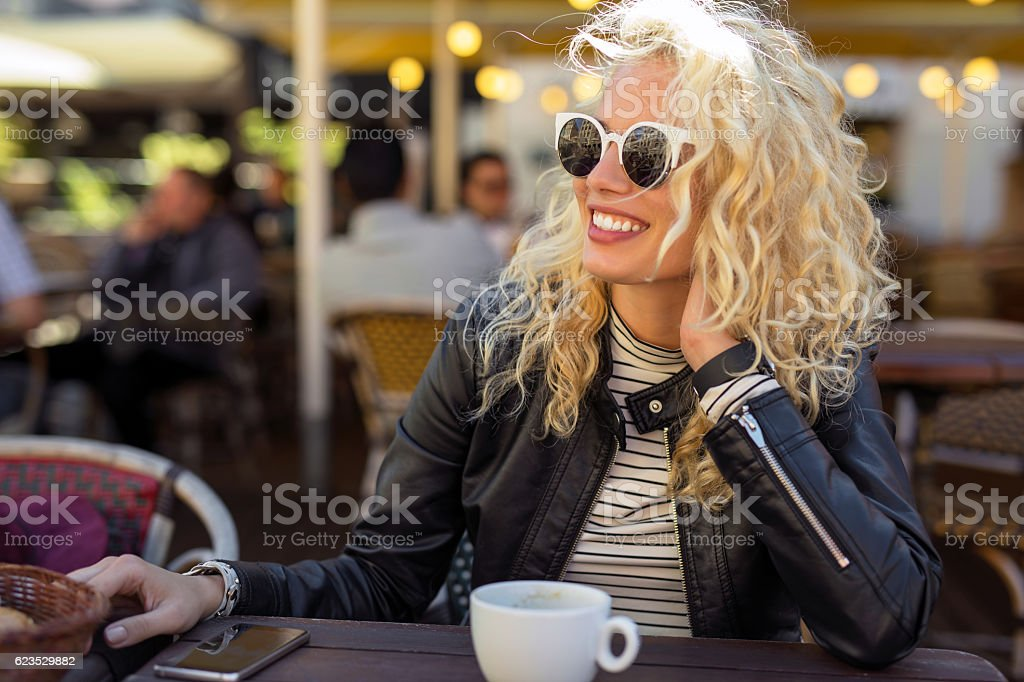 Happy and carefree woman sitting at cafe stock photo