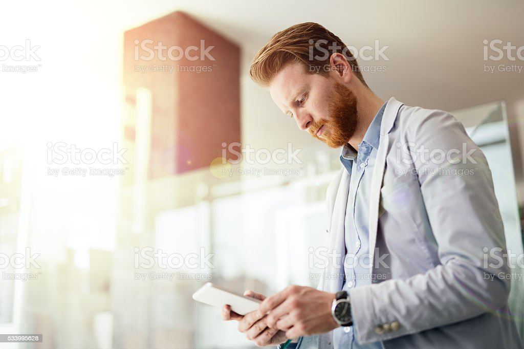 Happy and confident businessman using tablet stock photo