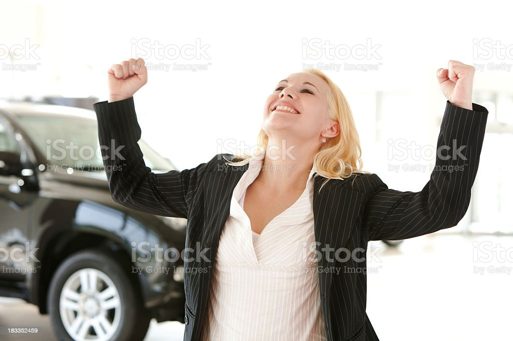 Happy and excited businesswoman in car showroom with hands raised royalty-free stock photo