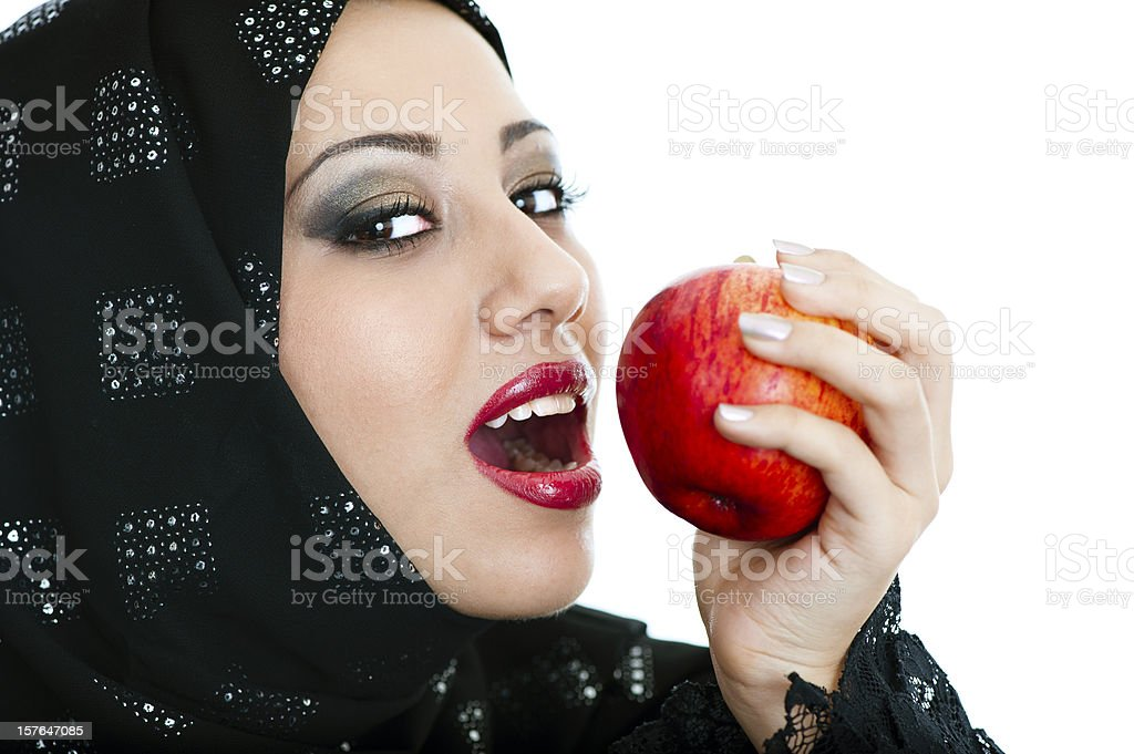 Happy and healthy Arabic girl eating an apple stock photo