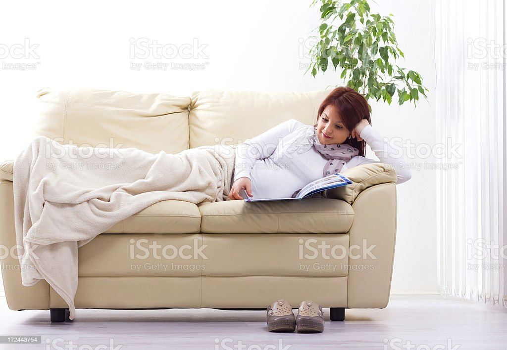 Happy and healthy pregnant woman on the couch. royalty-free stock photo