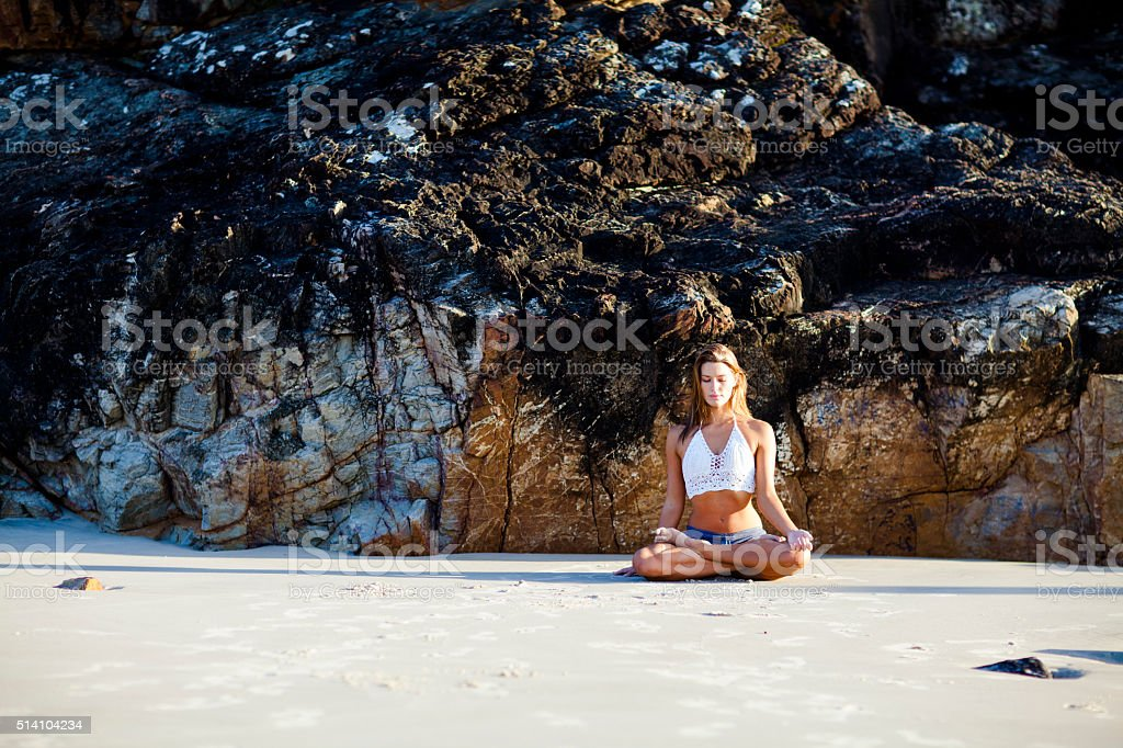Happy and healthy woman meditating on beach at sunrise. stock photo