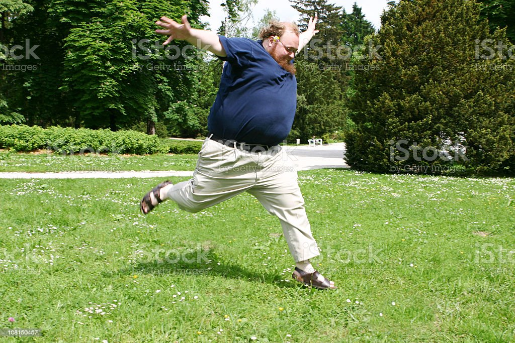Happy and Overweight Man Jumping in the Grass royalty-free stock photo