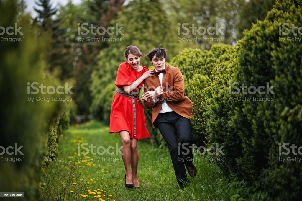 Happy and smiled couple running in love at park garden. Stylish man at velvet jacket and girl in red dress in love together stock photo