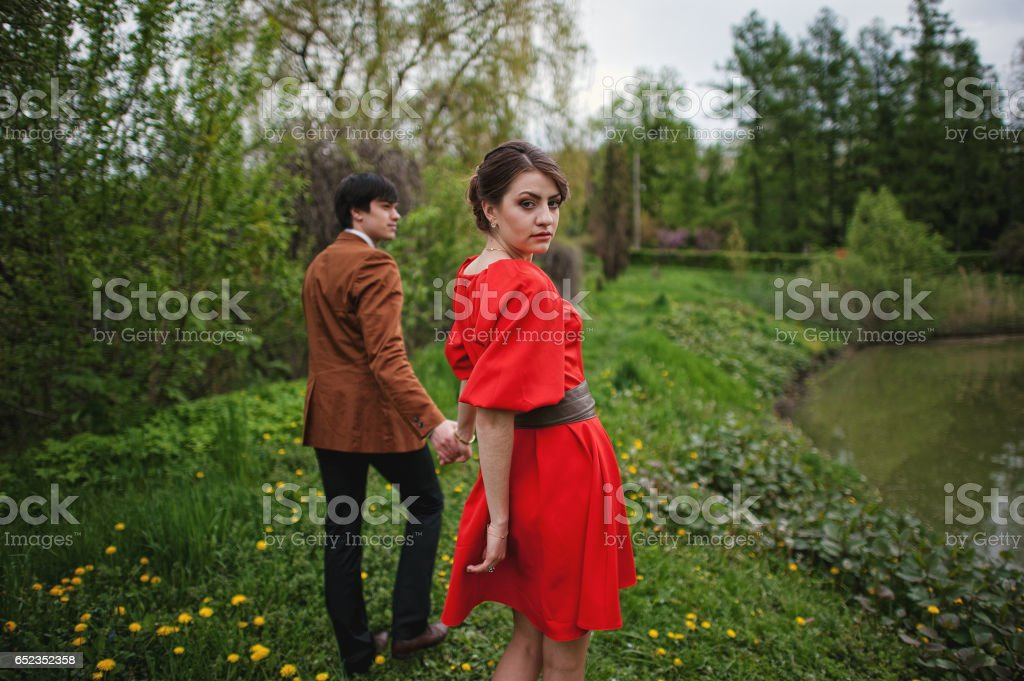 Happy and smiled couple walking in love at park garden. Stylish man at velvet jacket and girl in red dress in love together stock photo