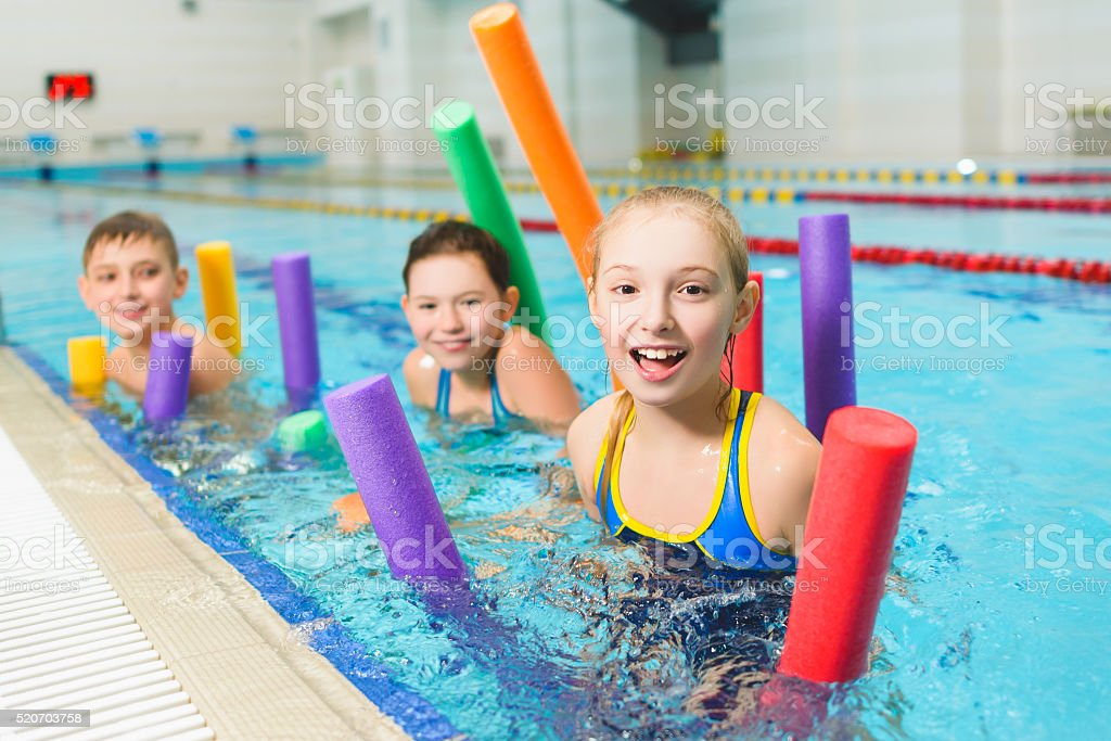 Happy and smiling group of children learning to swim with stock photo