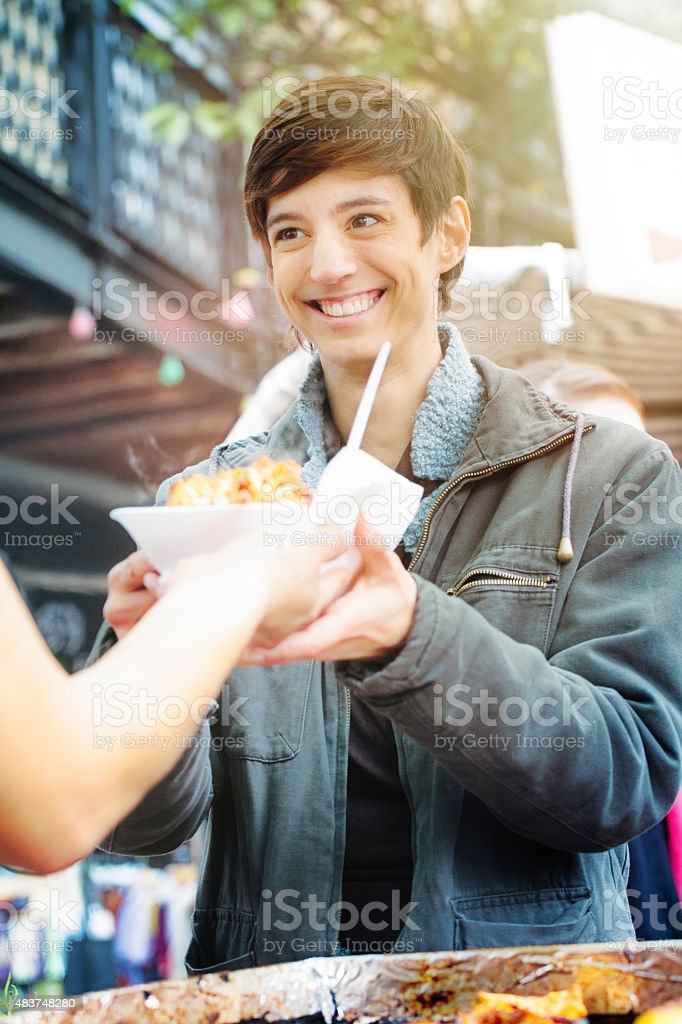 Happy androgynous young British woman smiling receiving street food stock photo