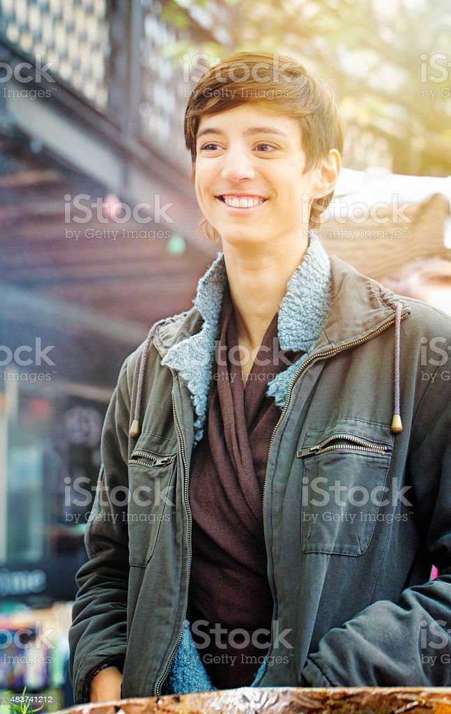 Happy androgynous young British woman smiling waiting for food outdoors stock photo