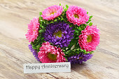 Happy Anniversary card with colorful daisy bouquet on wooden surface