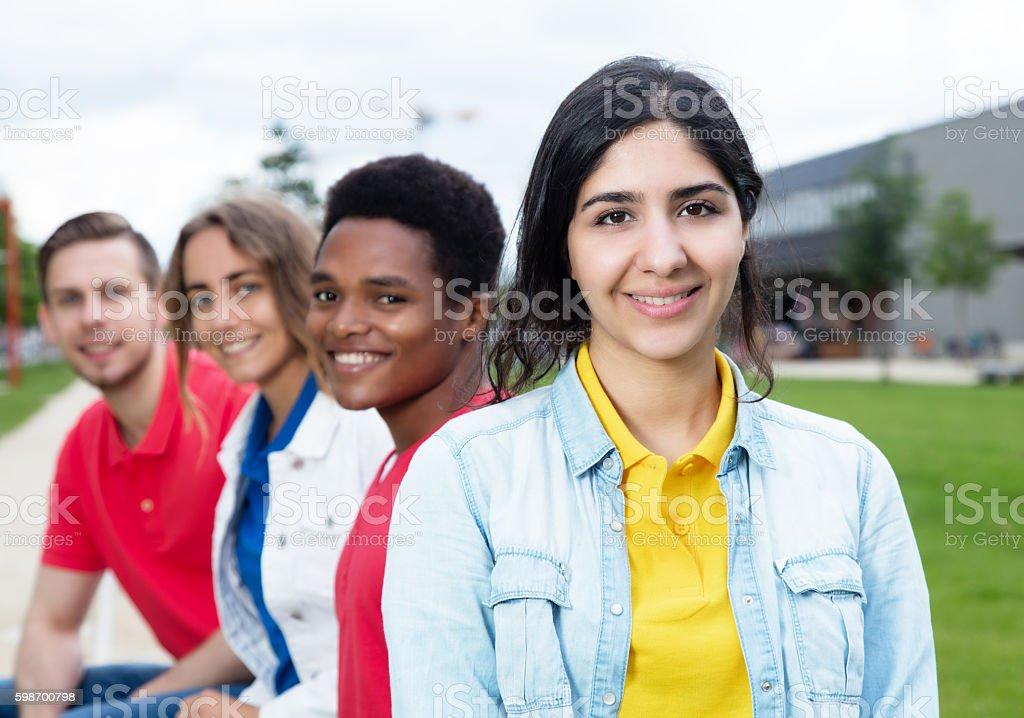 Happy arabian girl and multiethnic friends outdoor stock photo