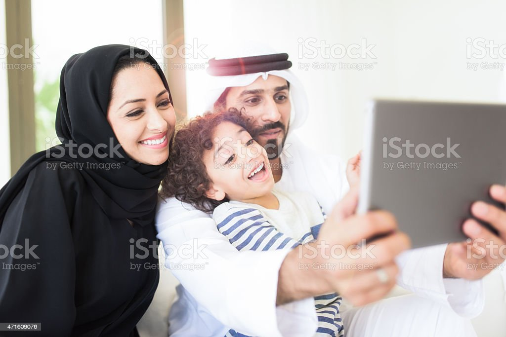 Happy Arabic family using a tablet together stock photo