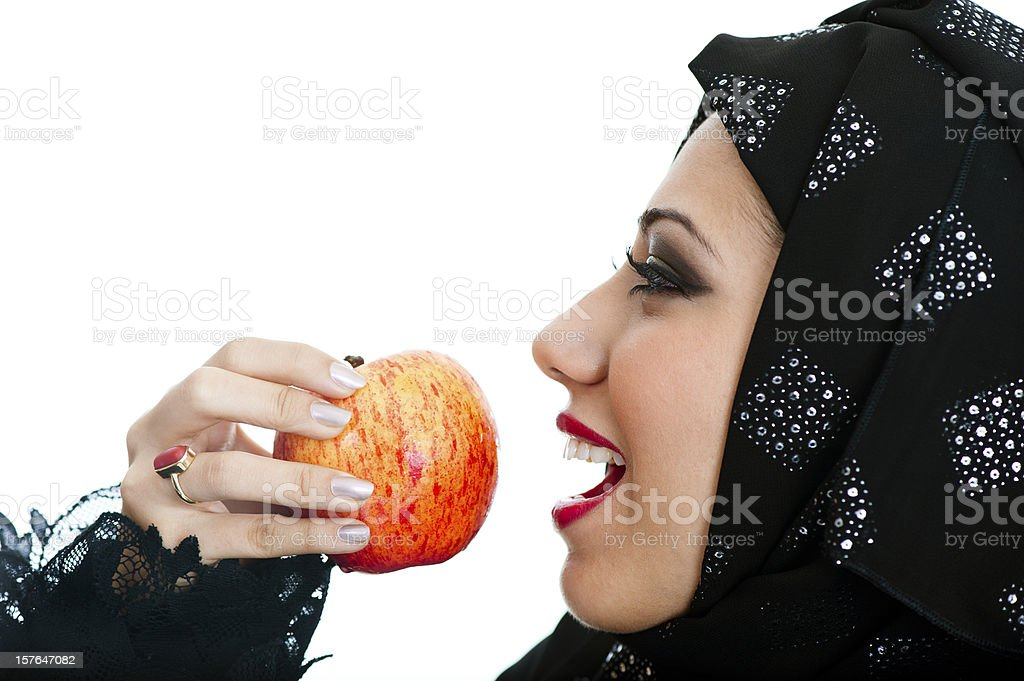 Happy Arabic girl eating an apple royalty-free stock photo