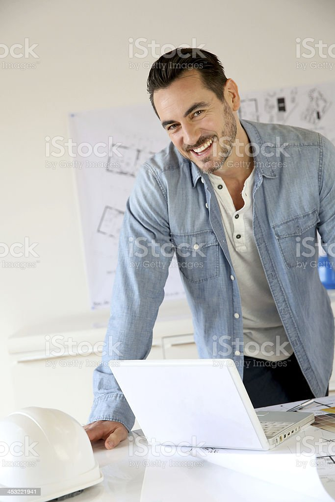 Happy architect standing in office looking at computer royalty-free stock photo