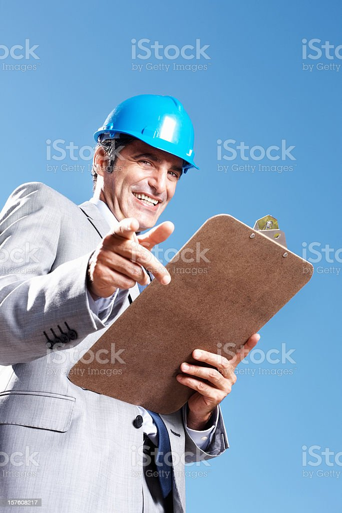 Happy architect with a clipboard smiling against sky royalty-free stock photo