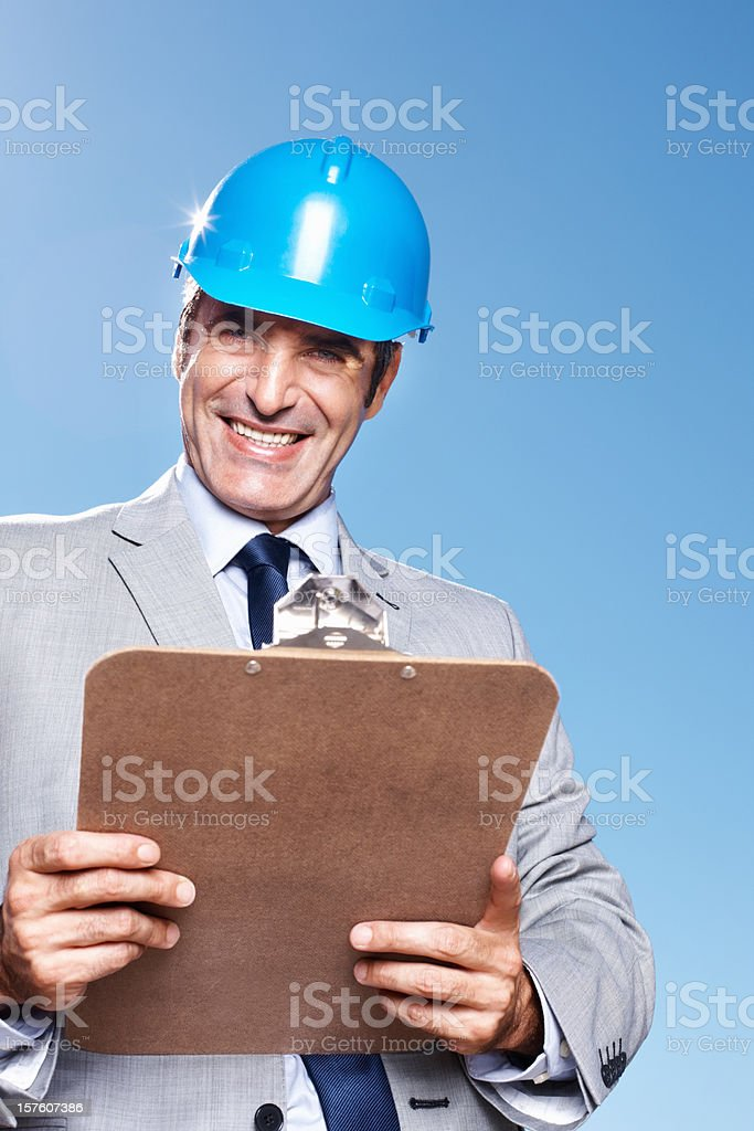 Happy architect with clipboard standing against blue sky royalty-free stock photo
