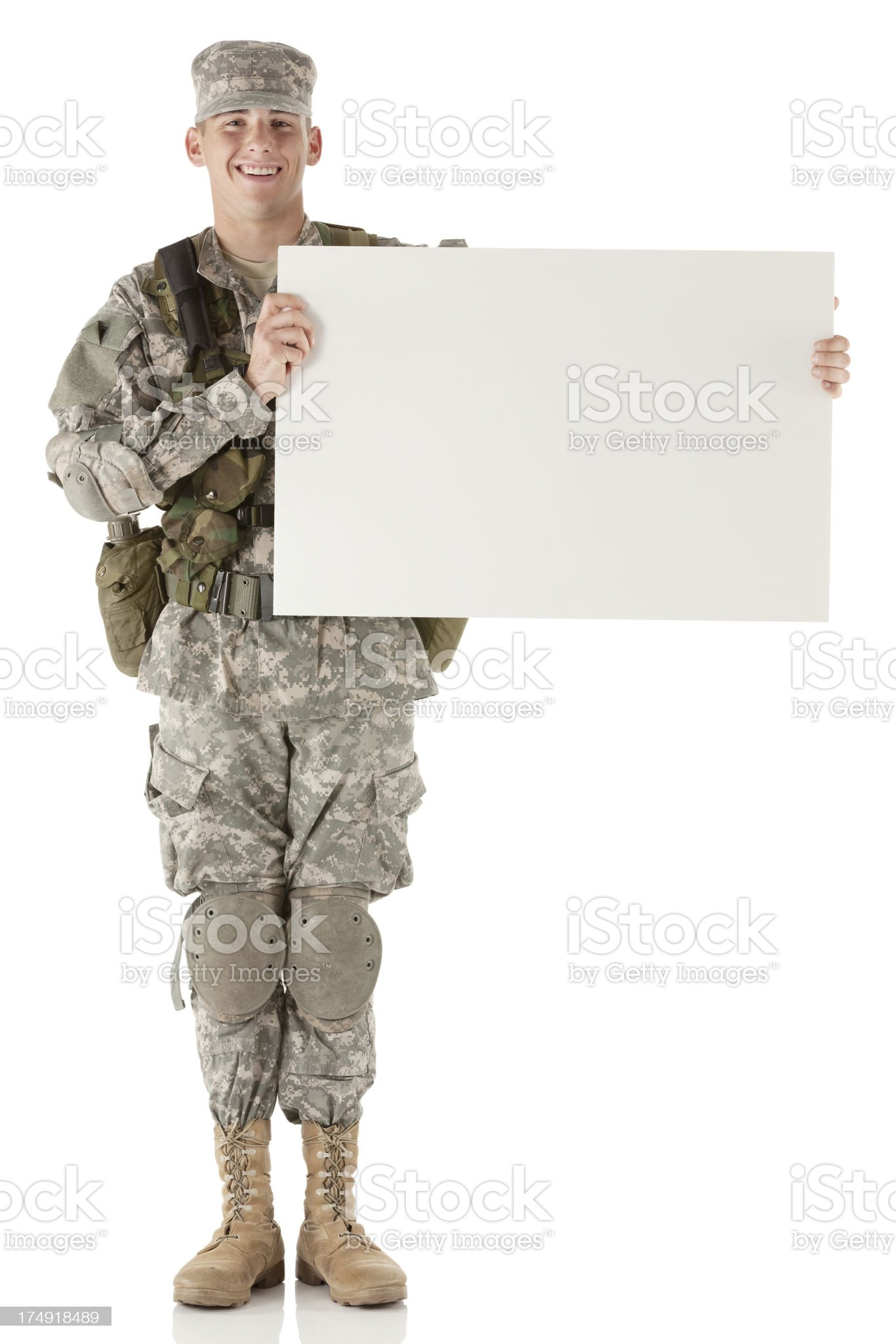 Happy army soldier holding a whiteboard royalty-free stock photo