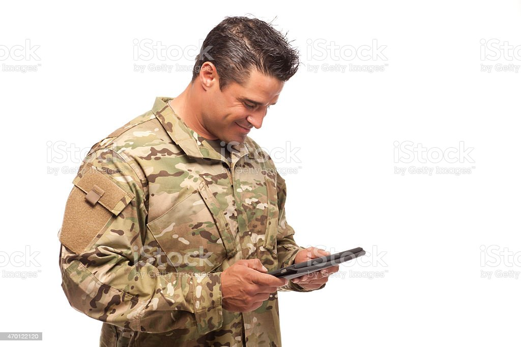 Happy army soldier reading digital tablet stock photo