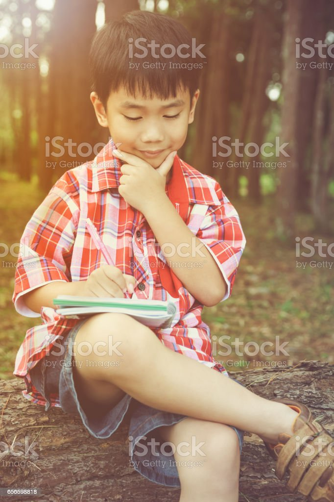 Happy asian boy reading a book. Education concept. Vintage style. stock photo