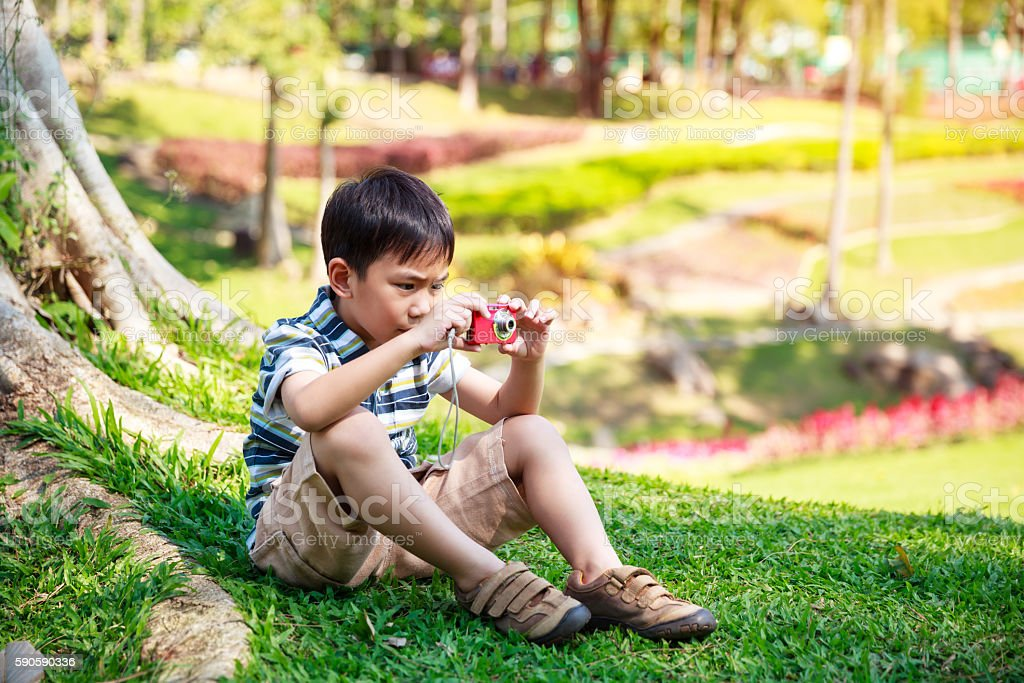 Happy asian boy with camera relaxing outdoors in the daytime stock photo