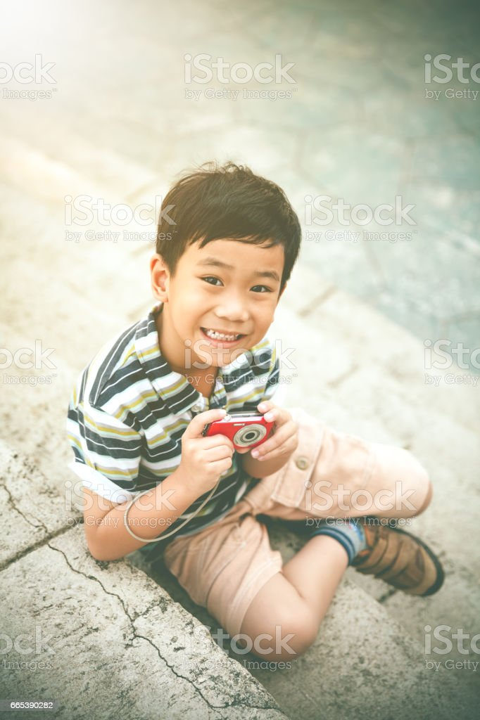 Happy asian boy with camera relaxing, travel on vacation. stock photo
