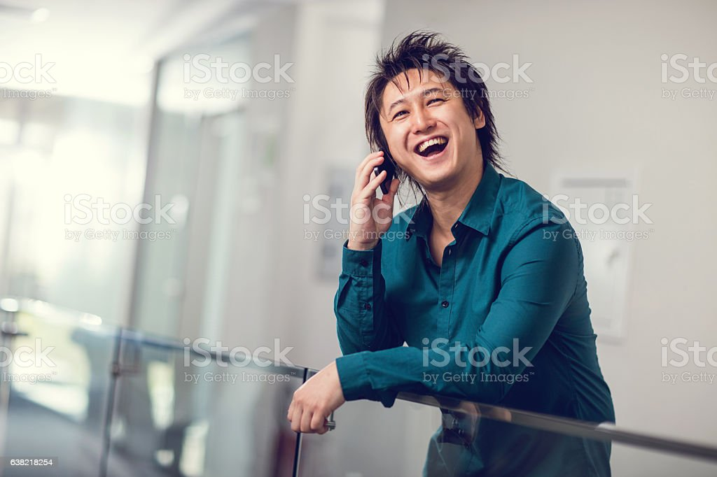 Happy Asian businessman talking over cell phone in a lobby. stock photo