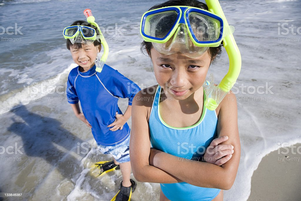 Happy Asian children with masks, snorkels and fins at beach royalty-free stock photo