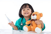 Happy Asian Chinese little girl examine teddy bear with thermome