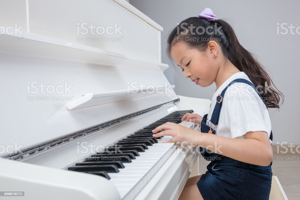 Happy Asian Chinese little girl playing classical piano at home stock photo