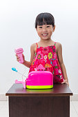 Happy Asian Chinese little girl pretending as cashier with toys
