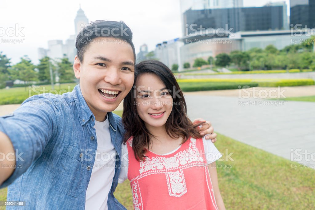 Happy Asian couple taking a selfie stock photo